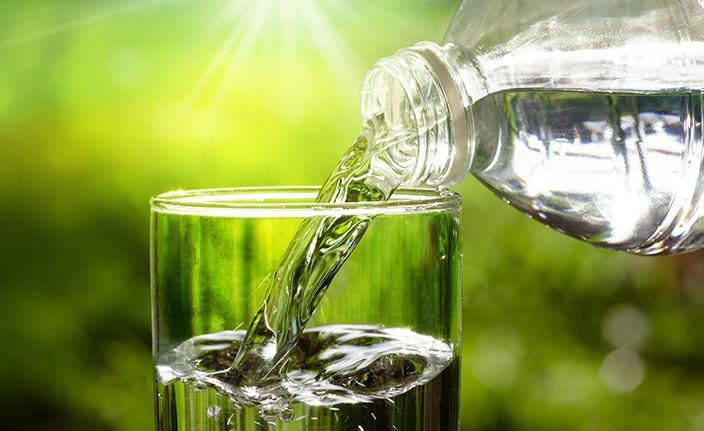 Pullosta kaadetaan vettä juomalasiin