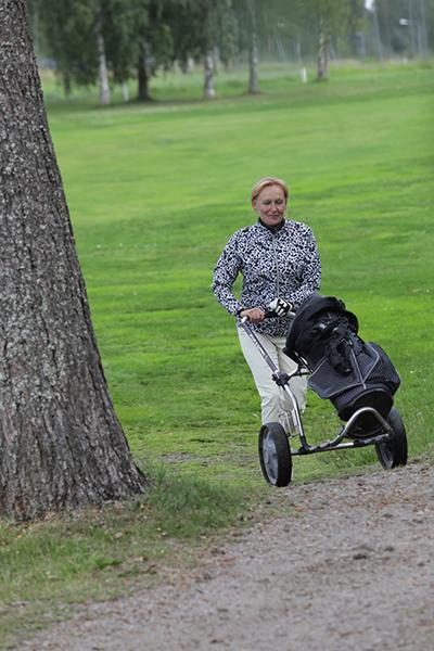 Maija Puranen työntää golfkärryä
